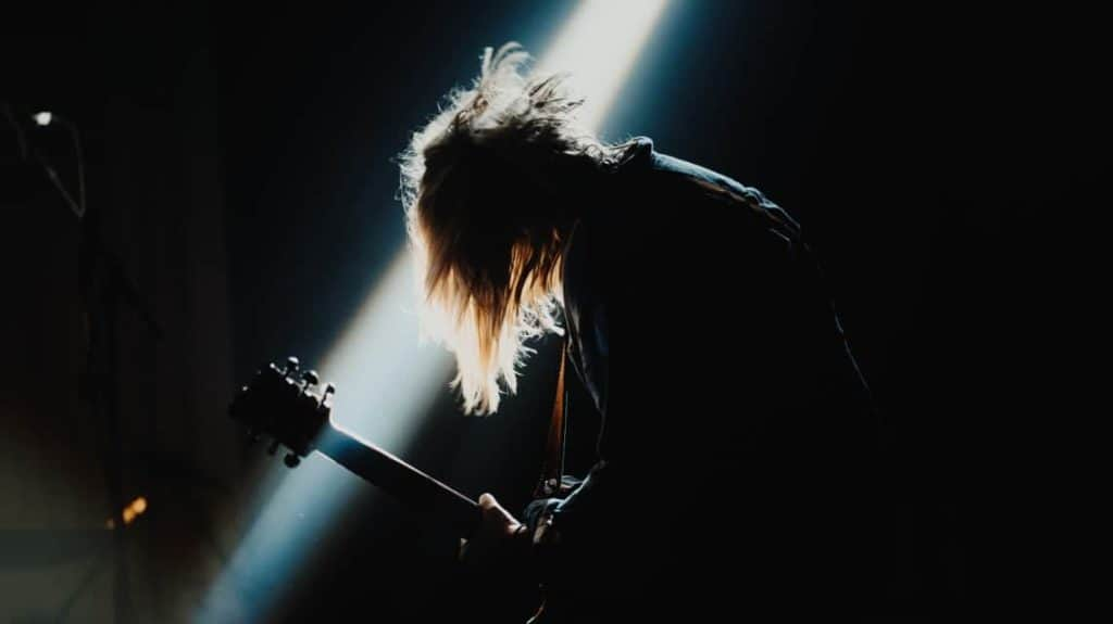 Musician playing guitar on stage